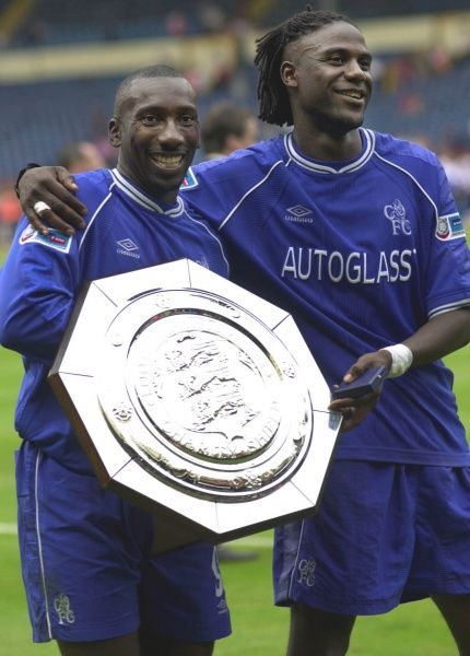 This picture can only be used within the context of an editorial feature. Chelsea goalscorers Jimmy Floyd Hasselbaink (l) and Mario Melchiot with the Charity Shield trophy after defeating Manchester United 2-0 at Wembley