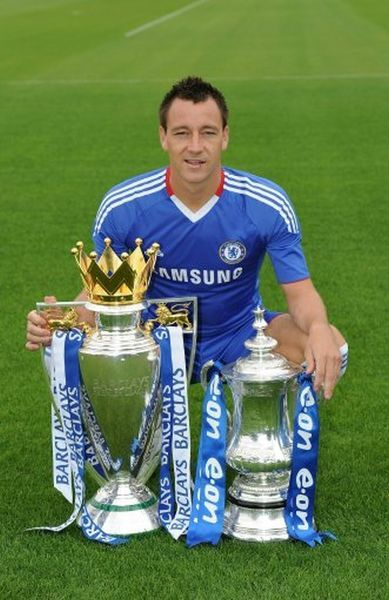 COBHAM, ENGLAND - AUGUST 27: John Terry of Chelsea with the Barclays Premier league trophy and the FA Cup during the 1st team photocall and Team Group at the Cobham Training ground on August 27, 2010 in Cobham, England
