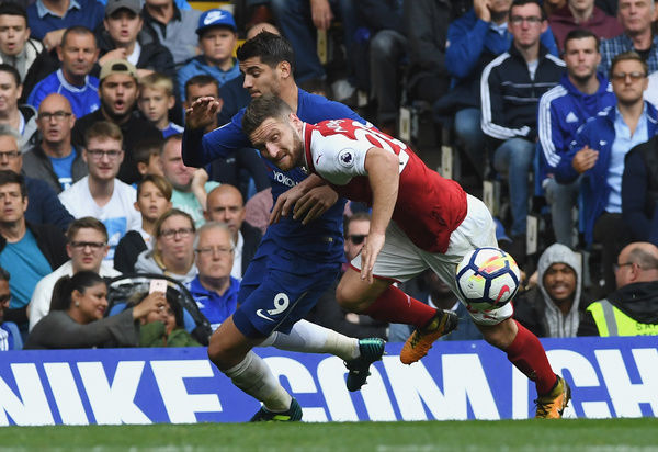 LONDON, ENGLAND - SEPTEMBER 17: Alvaro Morata of Chelsea and Shkodran Mustafi of Arsenal battle for possession during the Premier League match between Chelsea and Arsenal at Stamford Bridge on September 17, 2017 in London, England