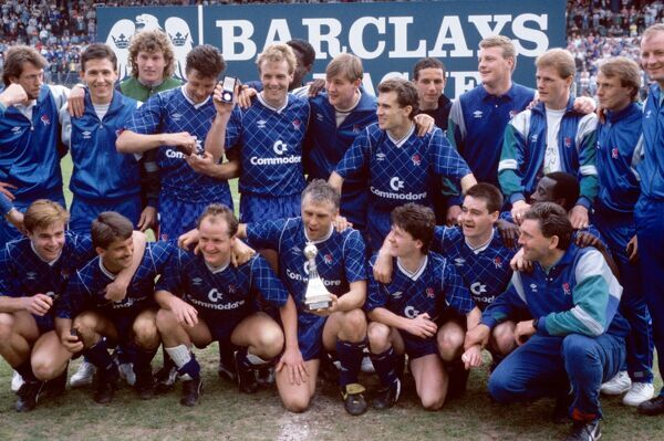 Chelsea players celebrate with the Division Two championship trophy after clinching the title with a 3-1 victory: (back row, l-r) Dave Mitchell, Kevin Hitchcock, Dave Beasant, Joey McLoughlin, Kerry Dixon, ?, ? Tony Dorigo, ?, ?, Gordon Durie