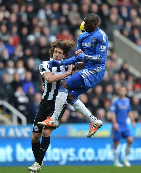 Newcastle United's Fabricio Coloccini (left) and Chelsea's Demba Ba (right) battle for the ball in the air
