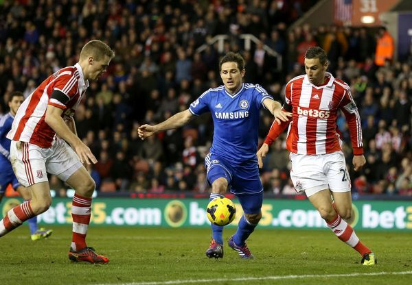 Chelsea's Frank Lampard (centre) and Stoke City's Geoff Cameron (right) battle for the ball during a Barclays Premier League match between Stoke City and Chelsea at the Britannia Stadium on 7th December 2013 in Stoke On Trent, England