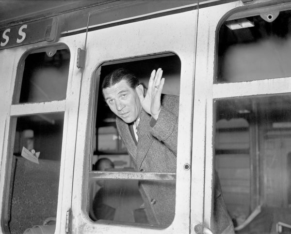 Chelsea manager Ted Drake waves from the window of a train carriage as the team leaves Victoria Station for their end-of-season European tour