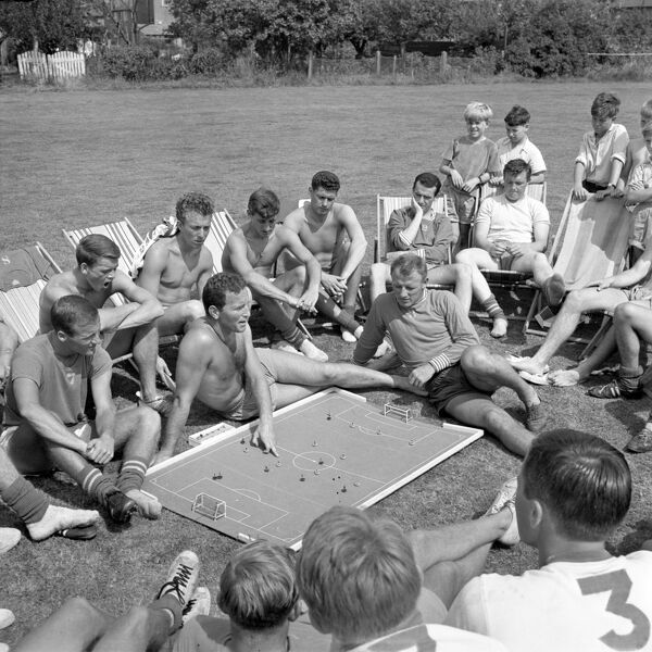 Chelsea players enjoy the sunshine as coach Dave Sexton (pointing) gives a tactical talk with the help of a Subbuteo pitch at Ewell in Surrey during the team's preparations for the forthcoming season