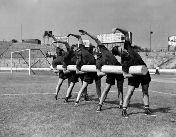 Members of the Chelsea team stretch while holding a 125lbs tree log during training