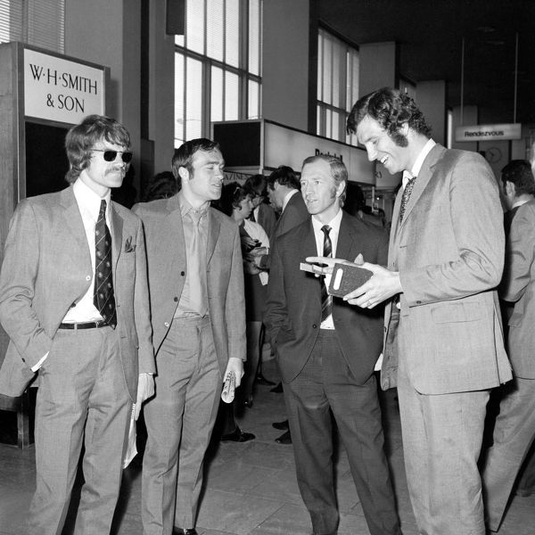 Chelsea's Peter Osgood (r) laughs at his own passport photo as he waits with teammates Ron Harris (second l) and Eddie McCreadie (l) for the team's flight to Athens, venue for the European Cup Winners Cup final