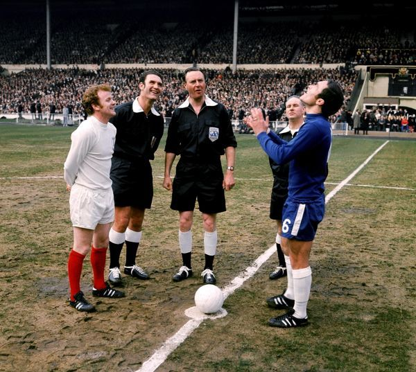 Leeds United captain Billy Bremner (l) and referee Eric Jennings (c) look on as Chelsea captain Ron Harris (r) waits for the coin to come down out of orbit