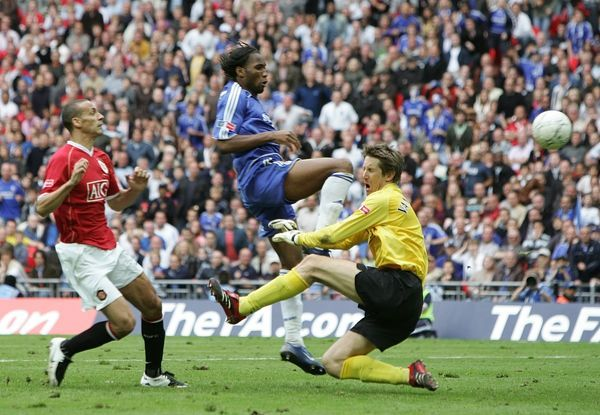 Chelsea's Didier Drogba scores past Manchester United's goalkeeper Edwin Van der Sar as Rio Ferdiand looks