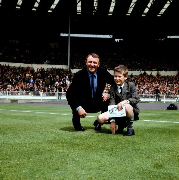 Chelsea manager Tommy Docherty with a small boy on the Wembley pitch before the game