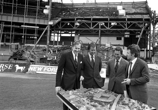 (L-R) Roger Bannister, Chelsea chairman Brian Mears, Chelsea manager Dave Sexton and architect John Darbourne examine a model of the proposed new developments at Chelsea's Stamford Bridge home, whilst demolition of the old stands continues in