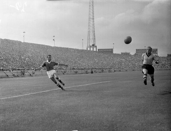 Chelsea's Peter Brabrook (l) crosses the ball beyond Wolverhampton Wanderers' Billy Wright (r)