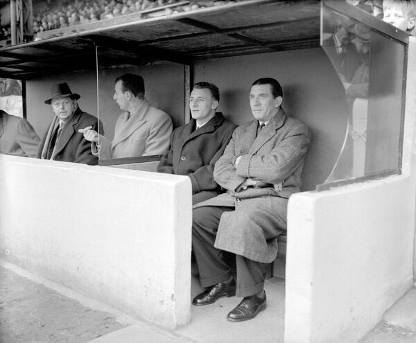 Chelsea manager Ted Drake (r) sits alongside his new player-coach Tommy Docherty (second r) in the dugout
