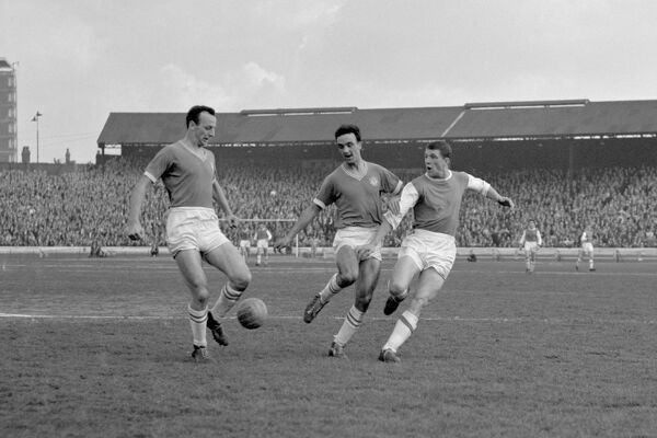 Arsenal's David Herd (r) shoots for goal as he is challenged by Chelsea's John Sillett (l) and Mel Scott (c)