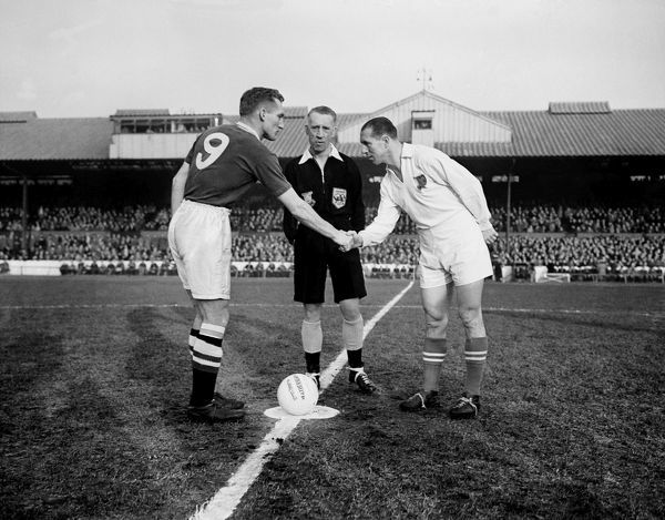 Chelsea captain Roy Bentley (l) shakes hands with Red Banner captain Nandor Hidegkuti (r) before the match, watched by referee Alf Bond (c)