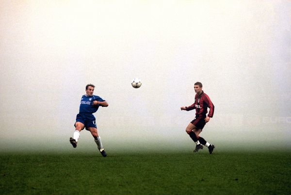 Albert Ferrer of Chelsea crosses the ball with AC Milan's Andriy Shevchenko moving in, in thick smoke in the San Siro after flares were let off by the Milan fans