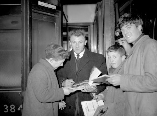 New Chelsea manager Tommy Docherty (c) signs autographs for young fans on the platform at Euston station